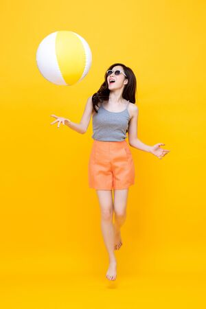 Foto de Happy young Asian woman in casual summer clothes playing beach ball in colorful yellow background - Imagen libre de derechos