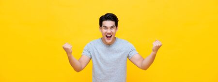 Photo pour Excited young Asian man raising his fists with smiling delighted face, yes gesture, celebrating success on yellow banner background - image libre de droit