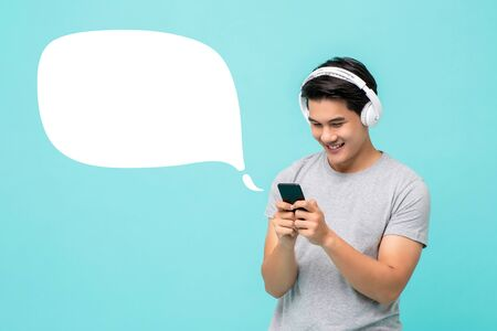 Happy young Asian man wearing wireless headphones listening to music from smartphone on light blue background with speech bubble