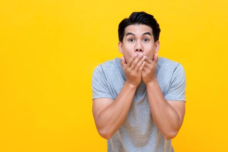 Photo pour Shocked man with hands covering mouth in colorful yellow background - image libre de droit