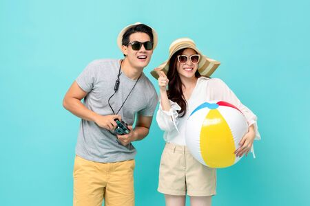 Photo for Lovely Asian couple in summer casual clothes with beach accessories studio shot isolated on light blue background - Royalty Free Image