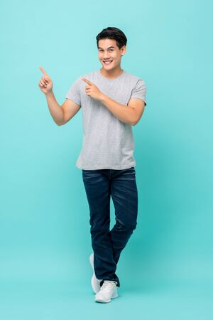 Foto de Confident smiling young Asian man pointing hands to empty space aside studio shot isolated on light blue background - Imagen libre de derechos