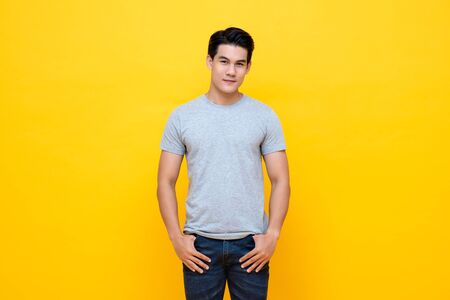 Photo for Handsome young Asian man in plain light gray t-shirt studio shot isolated on colorful yellow background - Royalty Free Image