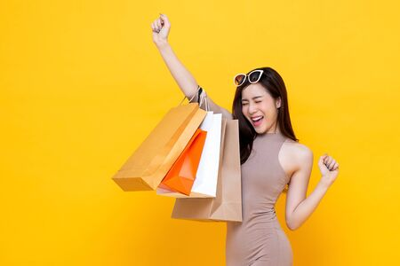 Photo pour Happy excited Asian woman carrying shopping bags with hand raising up studio shot isolated on colorful yellow background - image libre de droit