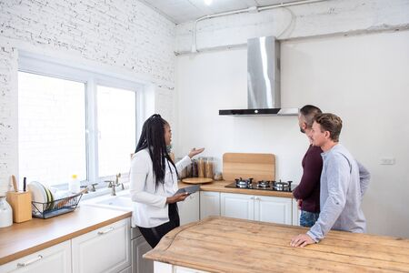 Photo pour Female real estate agent in kitchen showing gay couple around new house - image libre de droit