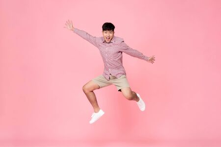 Photo for Energetic happy smiling young Asian man in casual clothes jumping studio shot isolated in colorful pink background - Royalty Free Image