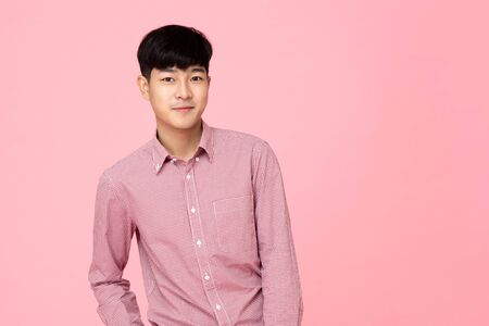 Photo for Portrait of young handsome Asian man in pink shirt, studio shot - Royalty Free Image