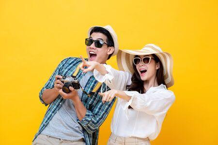 Photo pour Happy excited young Asian couple tourists in colorful yellow background - image libre de droit