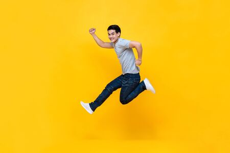 Photo for Energetic excited young Asian man in casual clothes jumping studio shot isolated in colorful yellow background - Royalty Free Image