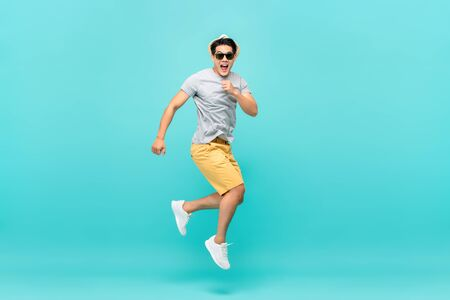 Photo pour Amazed handsome Asian tourist man jumping studio shot isolated on light blue background - image libre de droit
