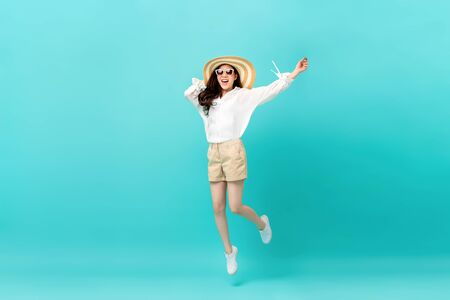 Photo for Studio shot of happy energetic asian woman wearing summer fashion attire jumping in mid-air motion isolated in light blue background - Royalty Free Image