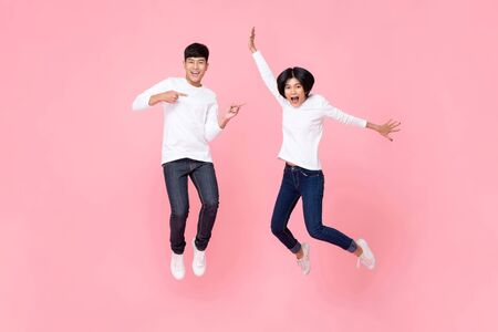 Foto de Studio shot of happy energetic asian couple wearing fashion paired attire jeans jumping in mid-air motion isolated in pink background - Imagen libre de derechos