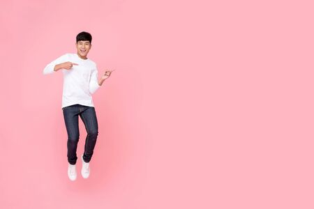 Photo pour Young cheerful energetic handsome Asian man jumping with hands pointing to copy space aside studio shot isolated on pink background - image libre de droit