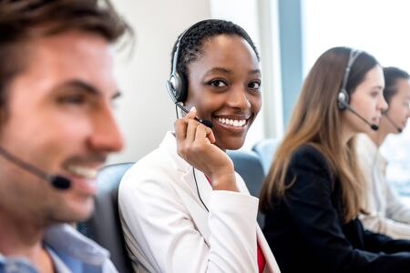 Foto de Smiling beautiful African American woman working in call center office with diverse team as the customer care operators - Imagen libre de derechos