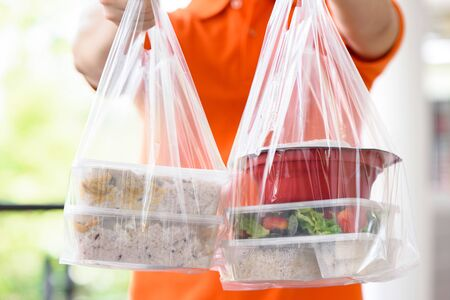 Photo for Asian food boxes in plastic bags delivered to customer at home by delivery man in orange uniform - Royalty Free Image
