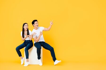 Photo pour Happy surprised attractive young Asian couple pointing and looking at blank space beside in yellow isolated stuidio background - image libre de droit