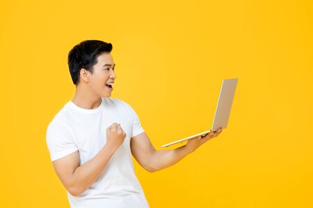 Photo pour Happy young Asian man looking at laptop computer and raising his fist doing yes gesture isolated on yellow background - image libre de droit