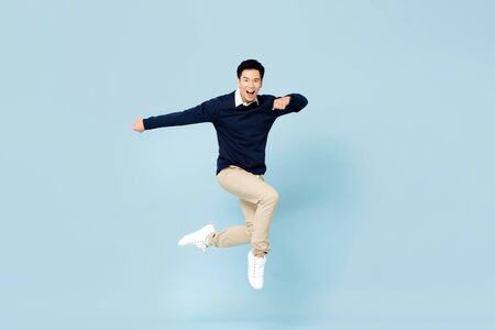 Photo pour Young handsome Asian man smiling and jumping in mid-air on light blue studio background - image libre de droit