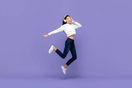 Photo pour Happy young Asian woman jumping and listening to music on headphones isolated on purple background - image libre de droit