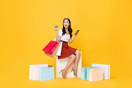 Photo pour Beautiful Asian woman sitting and carrying shopping bags with credit card and mobile phone in hands on yellow background - image libre de droit