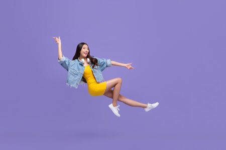 Photo pour Young beautiful smiling Asian girl floating in mid-air with hand pointing up and down isolated on purple background - image libre de droit