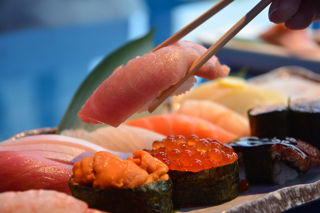 Photo for Chopsticks taking one piece of Otoro from Sushi Set nigiri and sushi rolls serving with soy sauce, Japan famous cuisine - Royalty Free Image