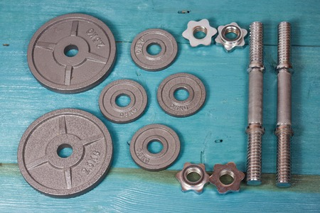 Top view of accessories for fitness in grey tone. Dumbbells, weight plates.