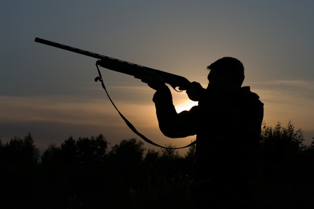 Silhouette of the hunter with a gun against the evening sky.
