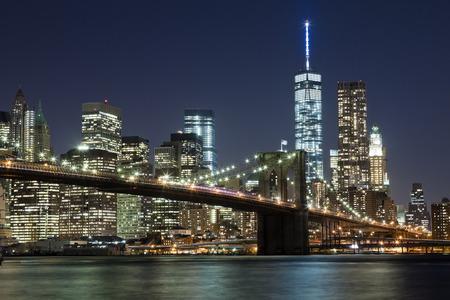 The New York City skyline at night w Brooklyn Bridge and Freedom tower