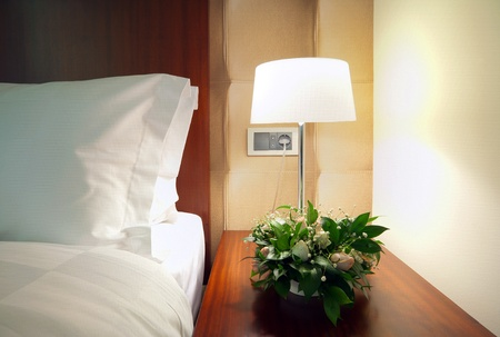 Detail of a room corner, lamp beside bed.