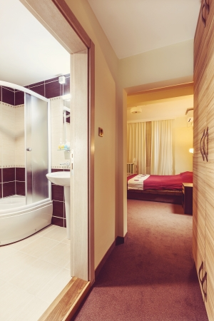 Interior of a hotel room, entrance with view on room and bathroom.