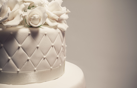 Foto de Details of a wedding cake, decoration with white fondant on white background. - Imagen libre de derechos