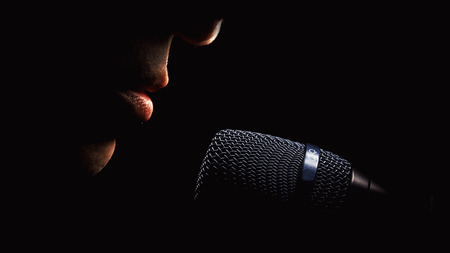 Part of a singer face, details of mouth and modern black microphone, on black background.