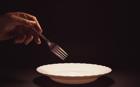 Conceptual composition, man's hand holding a metal fork over an empty plate, issue about food, poverty, etc.