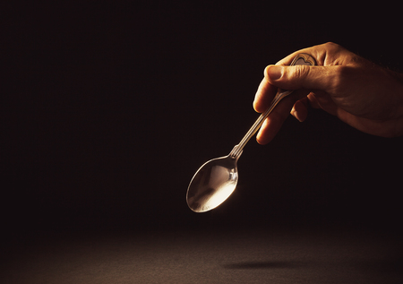 Conceptual composition, man's hand holding a metal spoon on empty background.