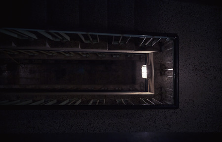 Dark ambiance of an old building interior, details of a staircase and lights.