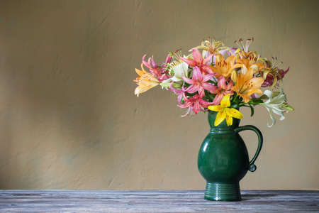 Photo pour lily in ceramic green jug on background wall - image libre de droit