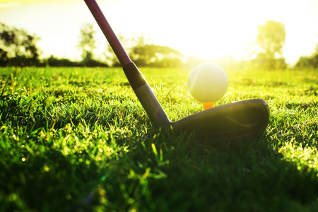 Foto de Golf clubs and golf balls on a green lawn in a beautiful golf course with morning sunshine.Ready for golf in the first short.Sports that people around the world play during the holidays for health. - Imagen libre de derechos