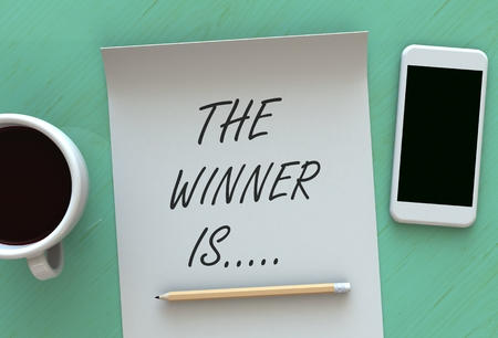 Photo for The Winner Is, message on paper, smart phone and coffee on table - Royalty Free Image