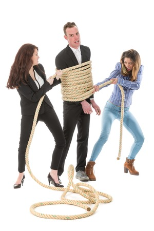 Two angry woman tying a business man with rope, isolated on a white background