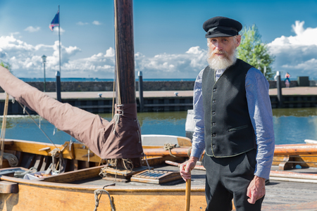 Urk, The Netherlands - September 02, 2017: Old sailor with stick, cap and beard standing for traditional wooden fishing boat in Dutch harbor of Urk