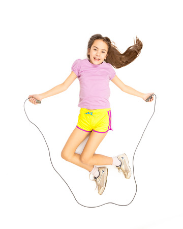 Isolated photo of cute active girl jumping with skipping rope