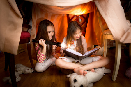 Two cute girls sitting under blankets and reading book with flashlight