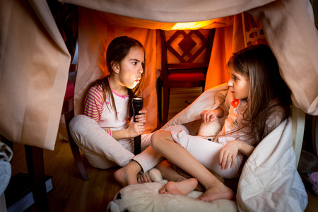 Portrait of elder sister telling scary story to younger one at late night in bedroom