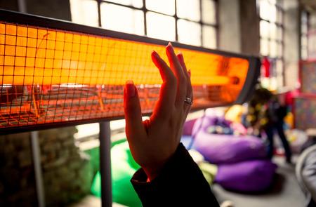 Closeup shot of woman warming hands at infrared heater