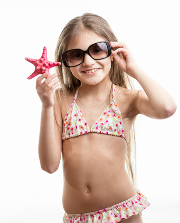 isolated portrait of happy smiling girl in sunglasses posing with red starfishの写真素材