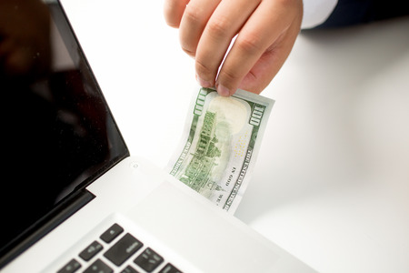 Conceptual photo of digital money transfer. Man inserting dollar banknote in the computer