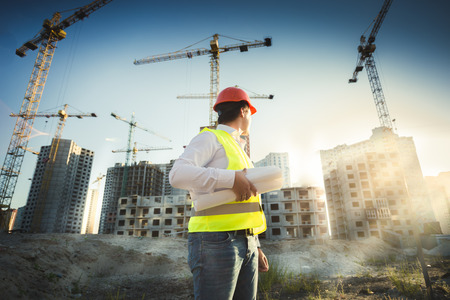 Man in hardhat and green jacket posing on building site at sunset