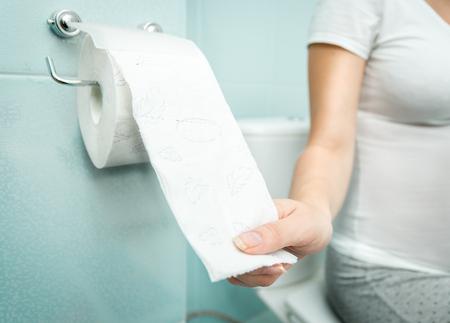 Foto de Closeup photo of woman sitting on toilet and using toilet paper - Imagen libre de derechos