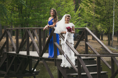 Beautiful bride and bridesmaid posing on wooden bridge over riverの写真素材